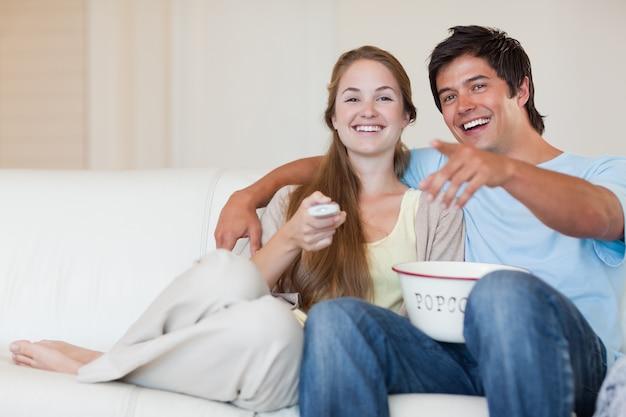 Lachend paar televisie kijken tijdens het eten van popcorn