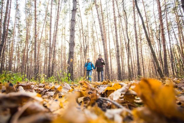 Lachend paar wandelen met rugzakken over herfst natuurlijke achtergrond.