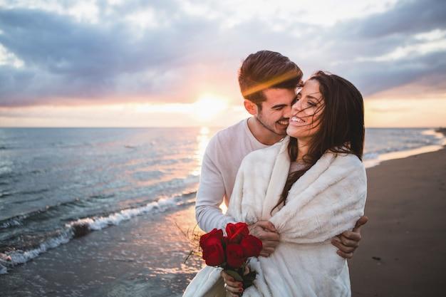 Lachend paar wandelen op het strand met een boeket rozen bij zonsondergang