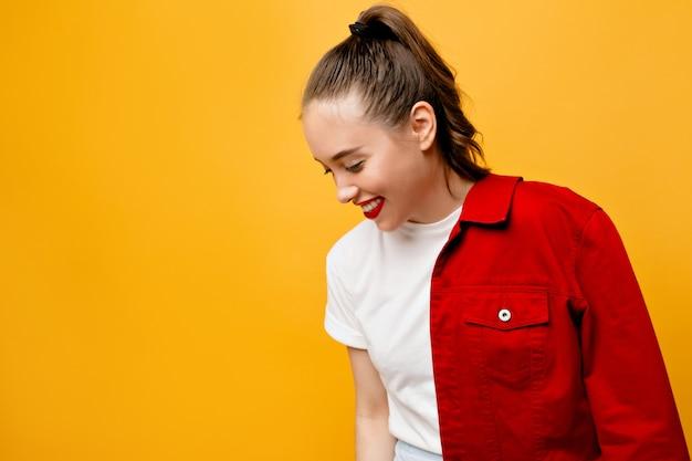 Lachend plezierig meisje met rood jasje dat zich op gele muur bevindt. binnenfoto van het gelukkige jonge vrouw stellen in goed humeur op heldere muur.
