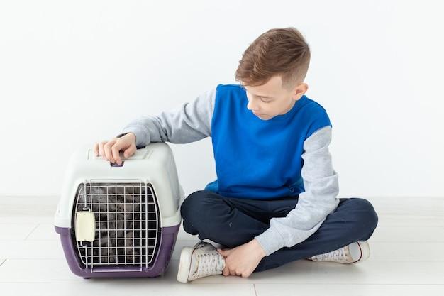 Lachend positief jongetje houdt een kooi vast met een scottish fold kat naast hem zittend op de vloer in een nieuw appartement. pet bescherming concept. copyspace