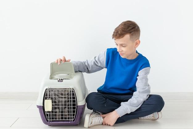 Lachend positief jongetje houdt een kooi vast met een scottish fold kat naast hem zittend op de vloer in een nieuw appartement