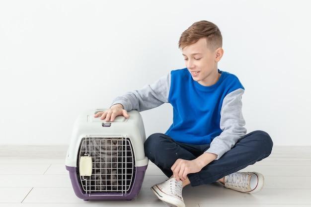 Lachend positief jongetje houdt een kooi vast met een scottish fold kat naast hem zittend op de vloer