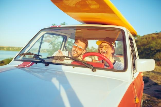 Lachend romantisch koppel zittend in de auto tijdens een roadtrip.