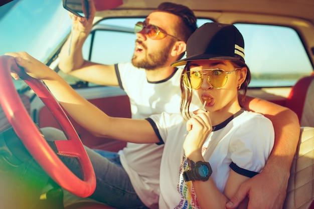 Lachend romantisch koppel zittend in de auto tijdens een roadtrip