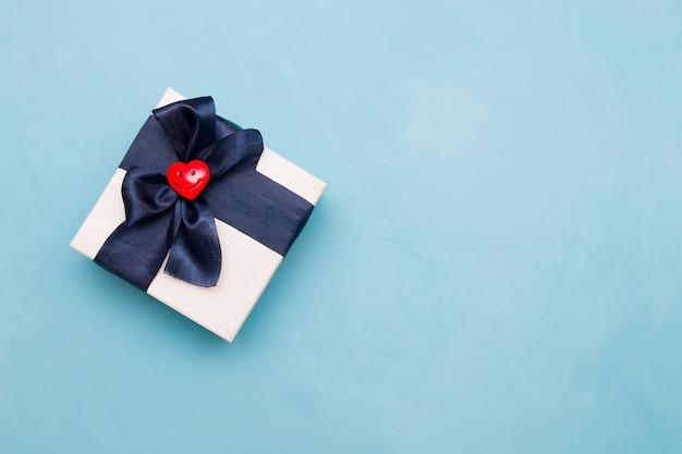Lachend rood hart op een geschenkdoos, blauwe achtergrond, kopieer ruimte