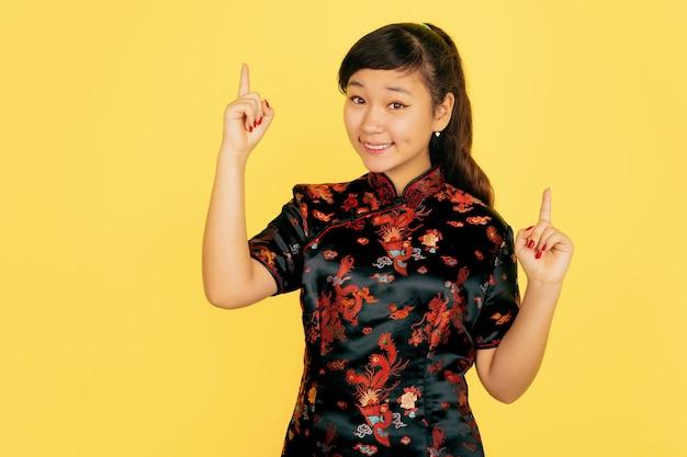 Lachend schattig, omhoog wijzend. gelukkig chinees nieuwjaar 2020. portret van aziatisch jong meisje op gele achtergrond. vrouwelijk model in traditionele kleding ziet er gelukkig uit. viering, menselijke emoties. copyspace.