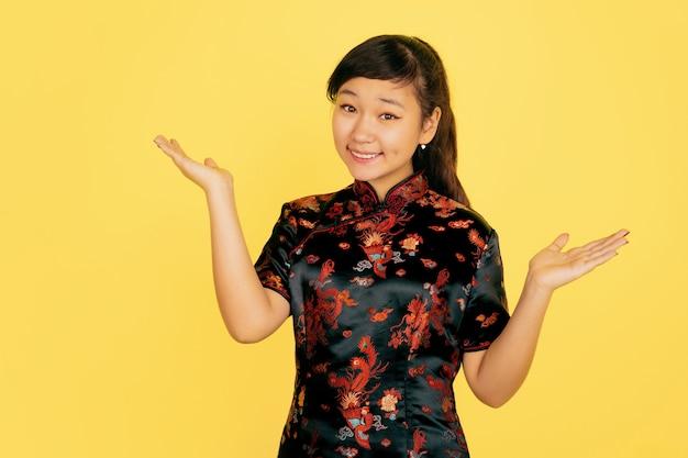 Lachend schattig, uitnodigend. gelukkig chinees nieuwjaar 2020. portret van aziatisch jong meisje op gele achtergrond. vrouwelijk model in traditionele kleding ziet er gelukkig uit. viering, menselijke emoties. copyspace.