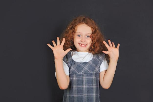 Lachend schoolmeisje dat open palm toont.