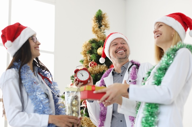 Lachend team van artsen in rode hoofdletters tegen de achtergrond van de kerstboom gefeliciteerd met