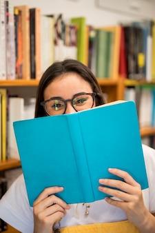 Lachend tienerschoolmeisje die gezicht behandelen met boek