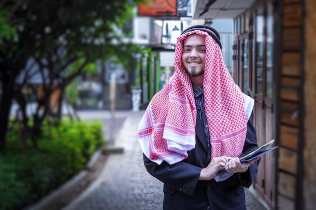 Lachend van zakelijke arabische man hand gebruiken om op de laptop te drukken. buiten