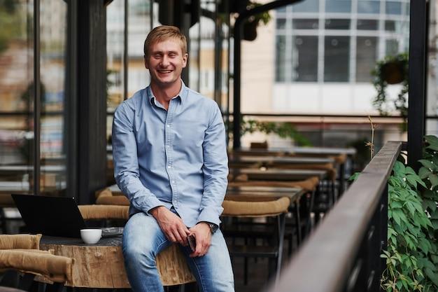 Lachend voor de camera. vooraanzicht van een man die overdag in een modern café zit met zijn laptop.