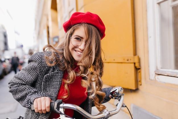 Lachend vrouwelijk model met lichtbruin haar met plezier op de fiets