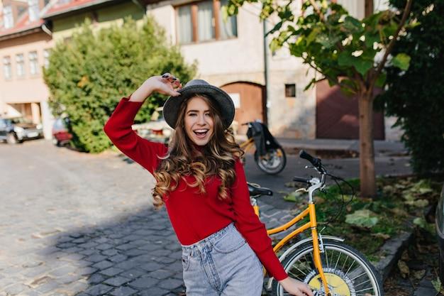 Lachend wit vrouwelijk model met glanzend krullend haar poseren in tuin met gele fiets