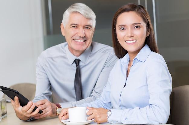 Lachend zakenman en vrouwelijke collega in cafe