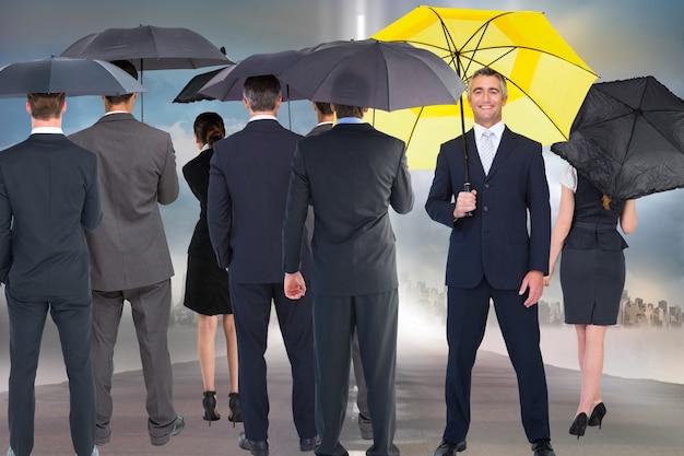 Lachend zakenman met gele paraplu