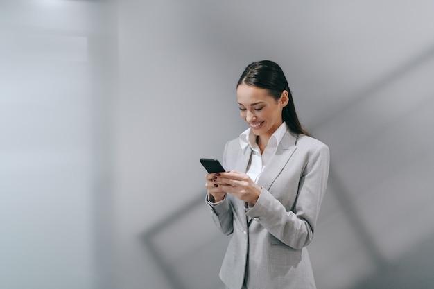 Lachende aantrekkelijke brunette met behulp van slimme telefoon in formele slijtage staande in de hal en het schrijven van e-mail op slimme telefoon. werk hard, droom groots, geef nooit op.