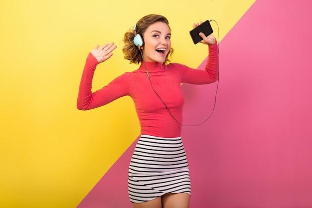 Lachende aantrekkelijke lachende opgewonden vrouw in stijlvolle kleurrijke outfit dansen en luisteren naar muziek in koptelefoon op roze gele achtergrond, mode-zomertrend