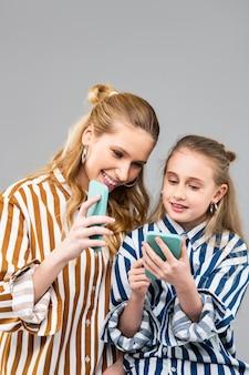 Lachende aantrekkelijke vrouw die iets interessants op het smartphonescherm laat zien aan haar nieuwsgierige jongere zus