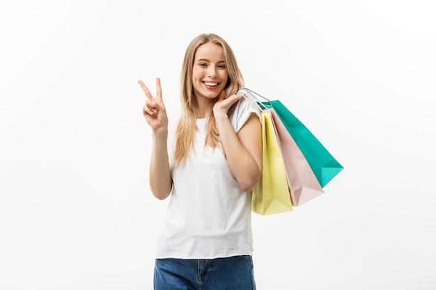 Lachende aantrekkelijke vrouw met boodschappentassen doen vredesteken op witte achtergrond met copyspace.