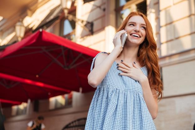 Lachende aantrekkelijke vrouw met lang haar praten op mobiele telefoon