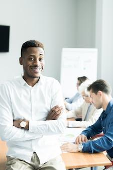 Lachende afrikaanse business trainer lesgeven studenten op cursus