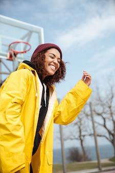 Lachende afrikaanse krullende jonge dame die gele laag draagt