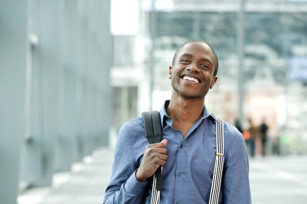 Lachende afrikaanse zakenman staande tas in gebouw