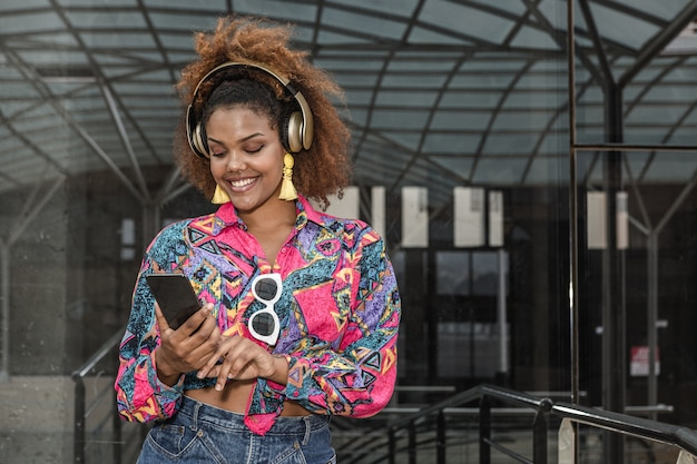 Lachende afro-amerikaanse dame in koptelefoon surfen op internet op smartphone