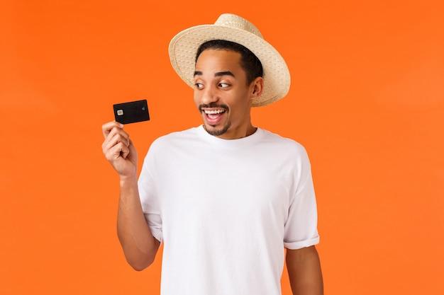 Lachende afro-amerikaanse knappe man in hoed te kijken naar creditcard
