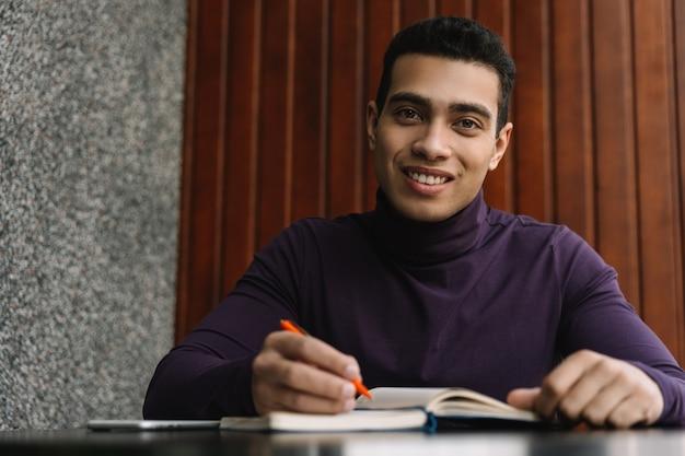 Lachende afro-amerikaanse student studeren, het maken van aantekeningen