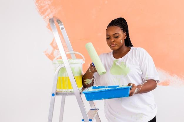 Lachende afro-amerikaanse vrouw schilderij binnenmuur van huis. renovatie, reparatie en herinrichting