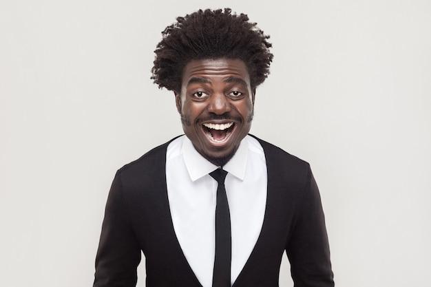 Lachende afro-zakenman die naar camera kijkt en brede glimlach. studio opname, grijze achtergrond