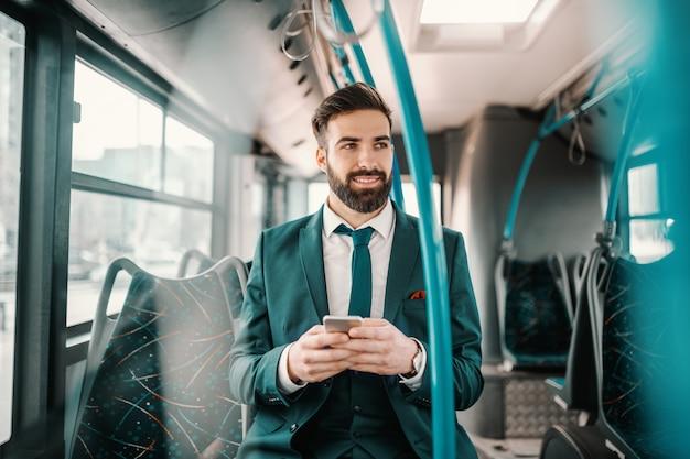Lachende ambitieuze bebaarde zakenman in turquoise pak zitten in de openbare bus en het gebruik van slimme telefoon. als je wilt vliegen, geef dan alles op dat je zwaar maakt.