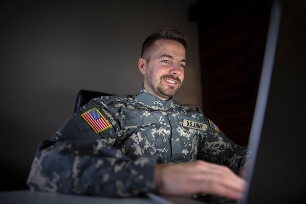 Lachende amerikaanse soldaat met usa patch vlag met behulp van laptopcomputer