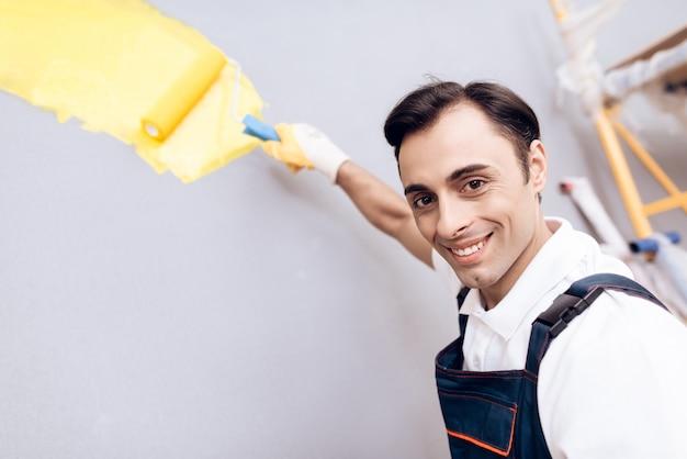 Lachende arabische meester met verf en penseel in de hand.