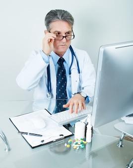 Lachende arts op zijn werkplek met computer, pillen, tabletten en patiëntgegevens geschiedenis