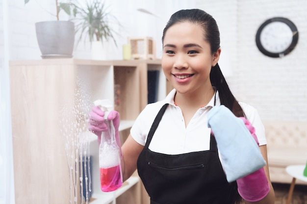Lachende aziatische dienstmeid wast venster met doek