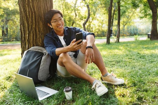 Lachende aziatische mannelijke student in bril met behulp van zijn smartphone zittend in de buurt van de boom in het park