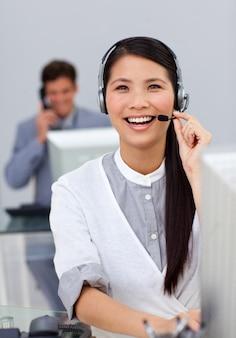 Lachende aziatische onderneemster met hoofdtelefoon op een computer