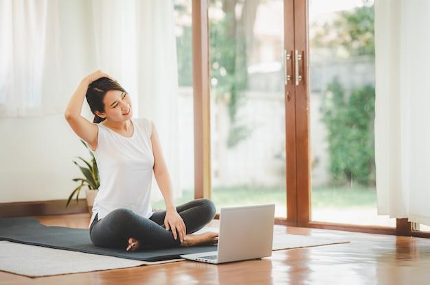 Lachende aziatische vrouw doet yoga nek uitrekken online klas van laptop thuis in de woonkamer.