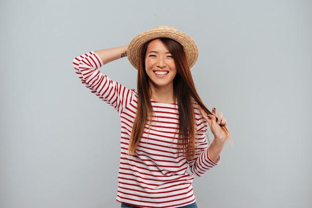 Lachende aziatische vrouw in sweater en hoed die camera bekijkt