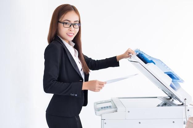 Lachende aziatische zakenvrouw met behulp van copier machine