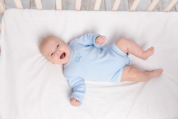 Lachende baby ligt in de wieg, schattige kleine jongen van zes maanden ligt in de kinderkamer op het bed en lacht