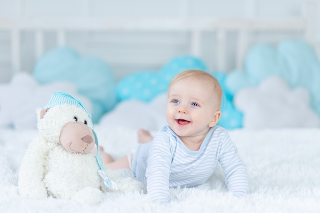 Lachende baby op bed met een speeltje werd 's ochtends wakker of gaat naar bed, blije baby