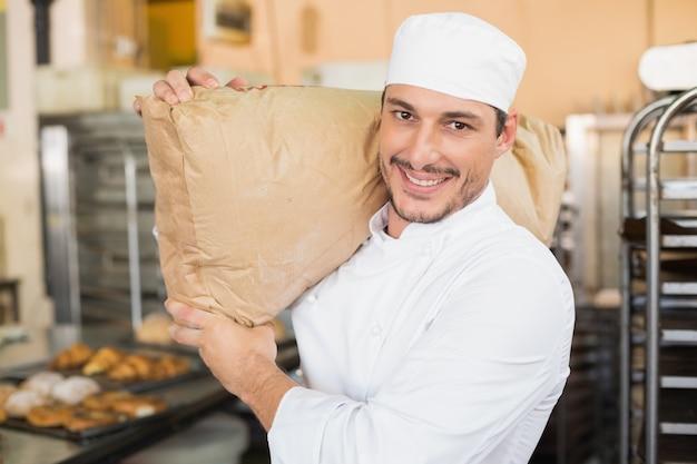 Lachende bakker met zak meel