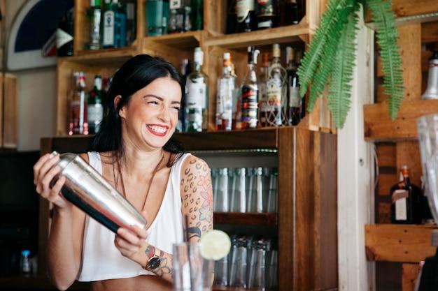Lachende barman die een cocktail maakt