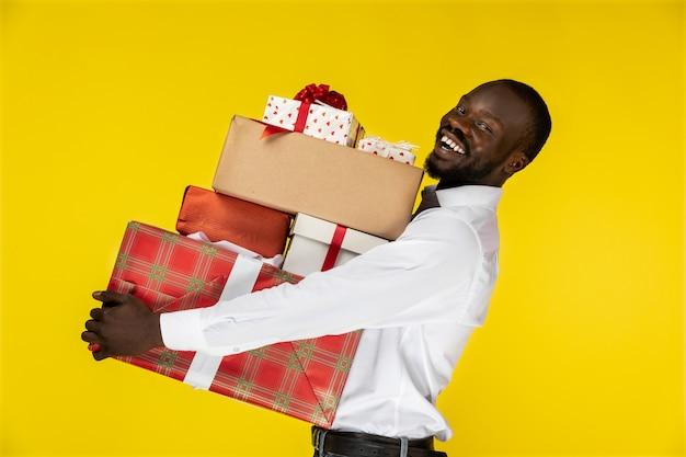 Lachende bebaarde jonge afro-amerikaanse man met veel cadeautjes