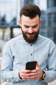 Lachende bebaarde jongeman sms-berichten op mobiele telefoon